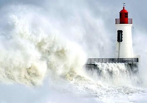 Vagues contre un phare en Bretagne
